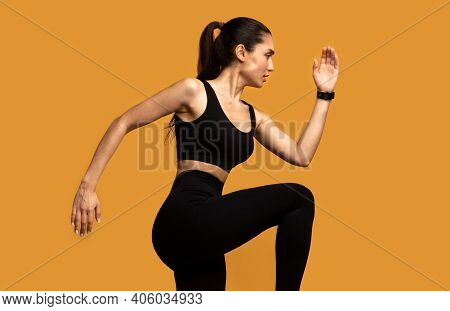 Sport Exercises And Healthy Lifestyle. Side View Portrait Of Determined Slim Young Lady Running And