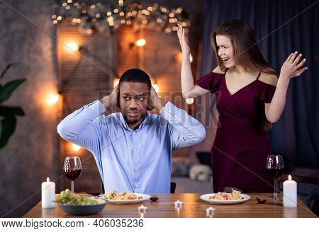 Young Interracial Couple Arguing During Dinner Date In Restaurant. Emotional Woman Shouting At Black