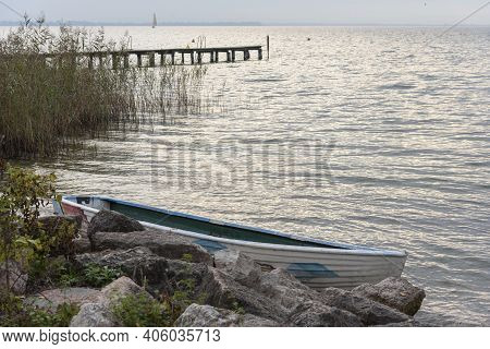 Lake Shore With Boat Moored Between Large Boulders. Background With Water, Wooden Jetty And Backgrou
