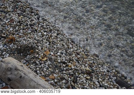 Lake Shore With Pebble Stones And Tree Trunk. White Water Waves.