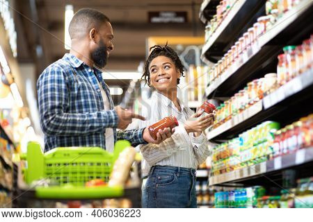 Happy African Family Couple Buying Food In Supermarket, Choosing Products Walking With Cart Along Ai