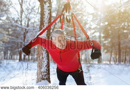 Outdoor Bungee Fitness. Athletic Senior Man Working Out With Suspension Training Straps At Snowy Win