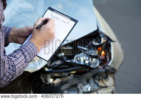 Male Hands With Paper Mock Up Auto Insurance Blank Against Destroyed Car In Car Crash Traffic Accide