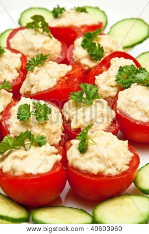 filled tomato appetizer on a plate ready to be served on a party poster