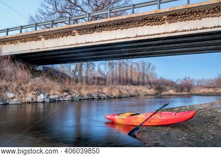 winter kayaking in Colorado - red whitewater kayak on shore of St Vrain Creek