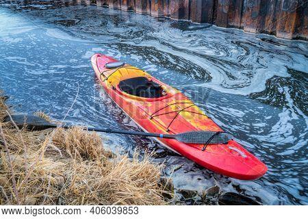 winter kayaking in Colorado - red whitewater kayak on shore of  St Vrain Creek near Platteville