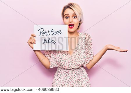 Young beautiful blonde woman holding positive vibes banner celebrating achievement with happy smile and winner expression with raised hand