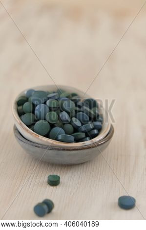 Spirulina Algae Green In Tablets In Round Ceramic Cups On A Light Wooden Background..dietary Supplem