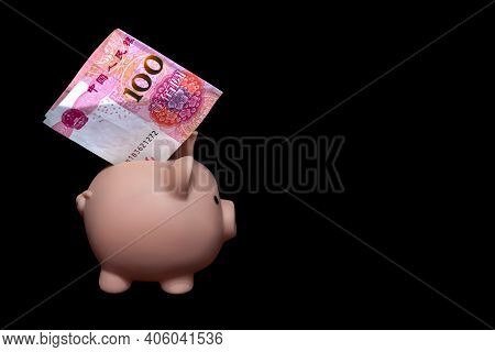 A Piggy Bank With A 100 Yuan Bill Inside On A Black Background. The Concept Of Saving Money. Careful