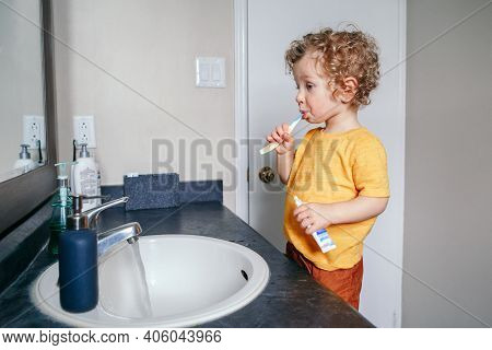 Little Caucasian Boy Toddler Brushing Teeth In Bathroom At Home. Health Hygiene And Morning Routine