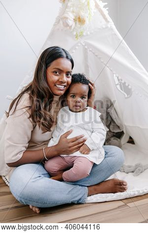 Happy Smiling Young Indian Mother Playing With Black Baby Girl Daughter. Family Mixed Race People Mo