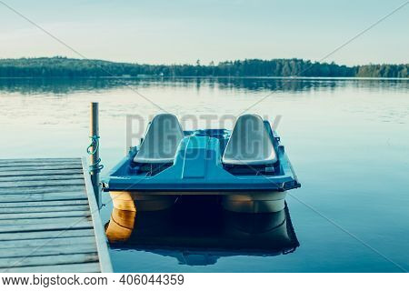 Old Blue Pedal Boat Tied To Wooden Dock Pier. Beautiful Idyllic Calm Serene Landscape Sunset Summer