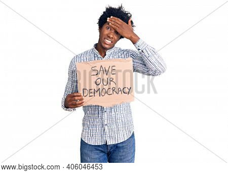 Handsome african american man with afro hair holding save our democracy protest banner stressed and frustrated with hand on head, surprised and angry face