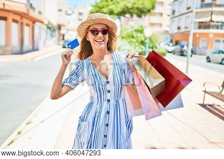 Young beautiful shopper woman smiling happy going to the shops sales holding shopping bags ourtdoors, smiling happy holding credit car