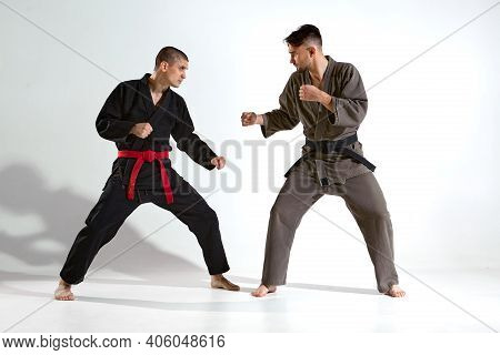 Guys In Kimono Fighting During Karate Workout On White Studio Backdrop With Copy Space, Martial Arts