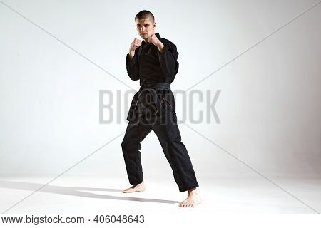 Sportive Guy Trainer In Black Kimono Fighter Posing In Karate Stance On Studio Background With Copy