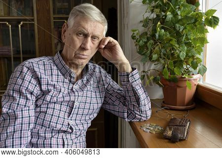 Portrait Of A Poor Sad Old Man With A Purse And Coins. The Concept Of Poverty, Low Income, Austerity
