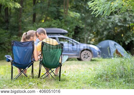 Happy Couple Sitting On Chairs At Campsite Hugging Each Other. Travel, Camping And Vacations Concept