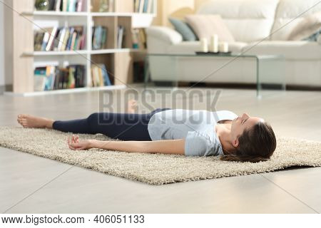 Woman Doing Yoga Savasana Pose After Exercise Lying On The Floor At Home