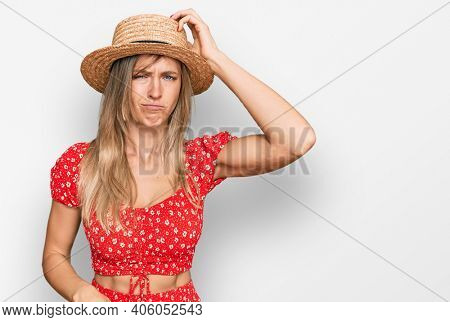 Beautiful caucasian woman wearing summer hat confuse and wonder about question. uncertain with doubt, thinking with hand on head. pensive concept.