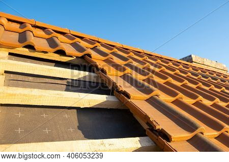 Overlapping Rows Of Yellow Ceramic Roofing Tiles Mounted On Wooden Boards Covering Residential Build