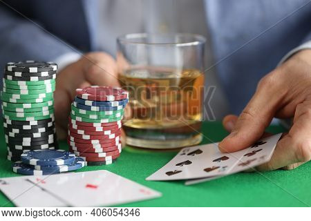 Male Hands Holding Glass Of Whiskey And Playing Cards In Casino Closeup. Gambling Addiction Concept