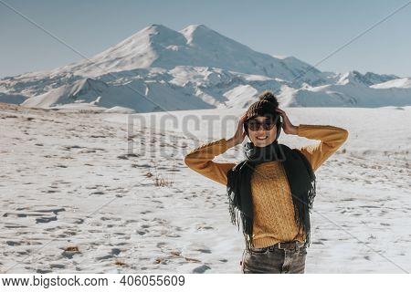 Woman Portrait In Sunny Weather In Winter In The Mountains. Girl In Warm Clothes Close-up Photo.