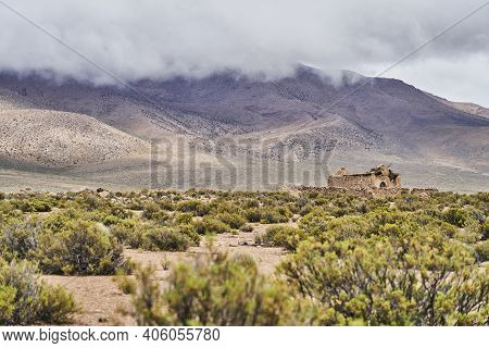 Old Ruin Of A Church, Adobe Building, With A Wall Made Of Cobble Stone Around It, Standing In The Hi