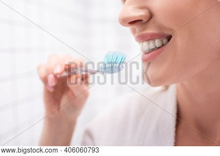Partial View Of Cheerful Woman Smiling While Holding Toothbrush With Toothpaste