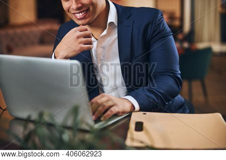 Joyous Male Entrepreneur Seated At His Computer