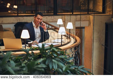 Joyous Male Entrepreneur Talking On The Smartphone