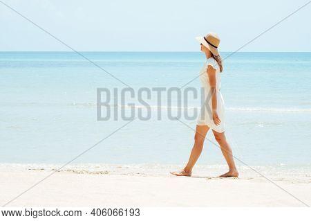 Beautiful Woman In A White Dress Walking On The Beach. Breathing Fresh Air Woman Near The Sea, Enjoy