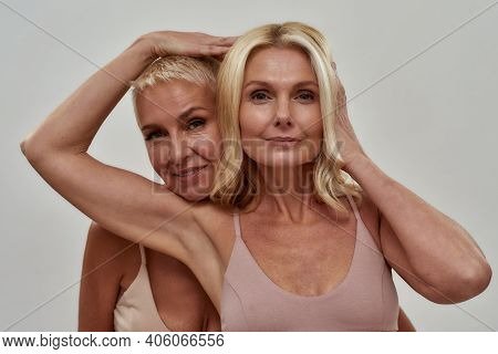 Studio Portrait Of Two Beautiful Blonde Women Looking At Camera, Standing Together, Posing Isolated