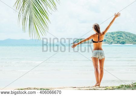 Rear View Of A Beautiful Brunette Young Girl With Raised Hands, Looking At Ocean. Freedom Concept