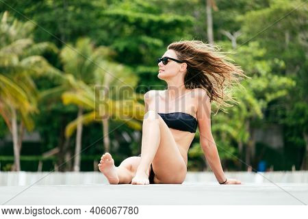 Portrait Of A Beautiful Young Woman Sunbathing On The Sea In A Swimsuit