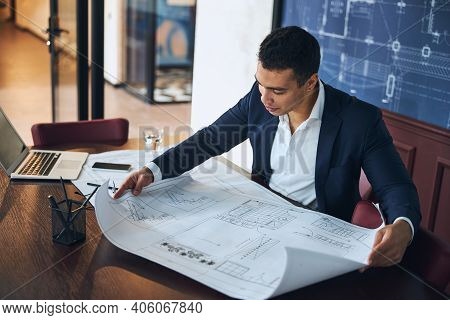 Dark-haired Professional Engineer Scrutinizing A Technical Drawing