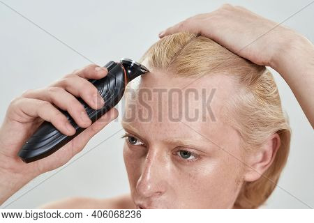 Close Up View Of Trimmer Used By Young Caucasian Blond Man With Long Hair On Head While Standing On
