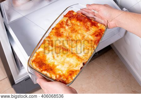 Frozen Food. Man's Hands Are Taking Frozen Lasagna From The Freezer Of The Fridge. Concept Of Ready