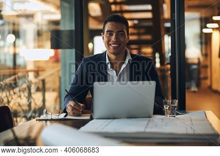 Joyous Draftsman Sitting At The Laptop In His Office