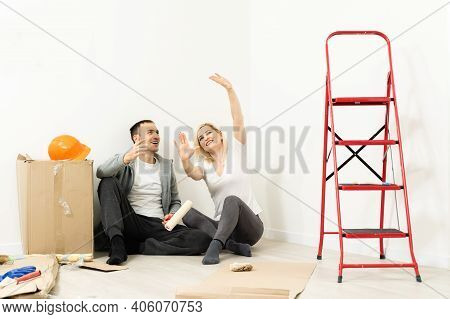 Closeup Portrait Of Adult Couple Sitting On Floor At Their Apartment And Planning Renovation Of Thei
