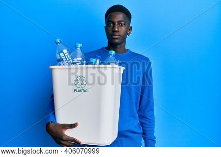 Young african american man holding recycling wastebasket with plastic bottles thinking attitude and sober expression looking self confident