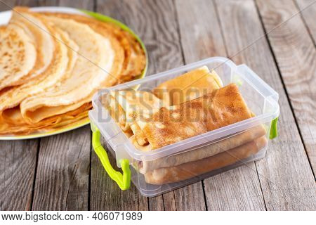 Frozen Pancakes In Container On A Wooden Background. Semi-finished Pancakes With Filling