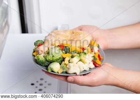 Frozen Food In The Freezer. Frozen Meat And Vegetables On A Plate. Concept Of Frozen Food, Long Term