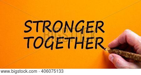 Stronger Together Symbol. Businessman Writing 'stronger Together', Isolated On Orange Background. Bu