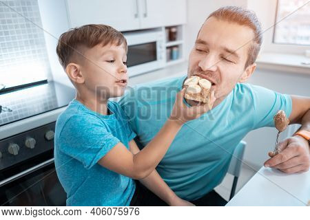Happy Kid Boy And Father Eating Healthy Peanut Butter Toast At Home Kitchen