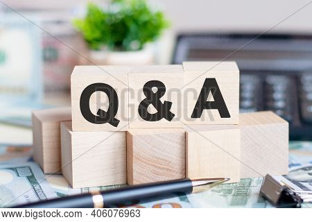 Concept Word Q And A On Wooden Blocks On Beautiful Background From Dollar Bills. The Word Q And A On