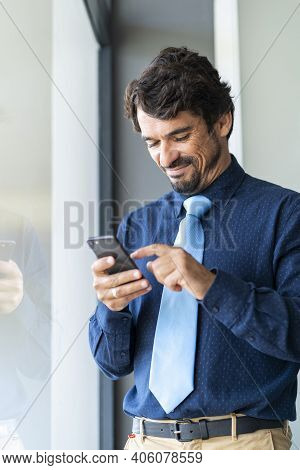 Businessman Smiling, Holding And Looking At His Smartphone. Happy Successful Male Portrait