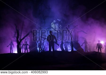 Man With Riffle Against Zombie Attack. Zombie Apocalypse. Scary View Of Blurred Zombies At Cemetery