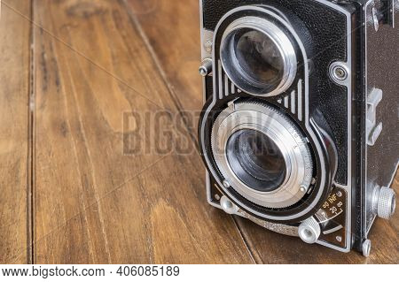 Detail Of The Lenses Of An Old Twin Lens Reflex Camera, On A Wooden Table, Antique And Classic Photo