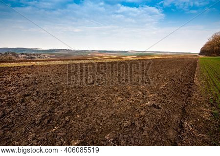 Arable Spring Field, Plowed Soil And Relief Hilly, Landscape In The Background